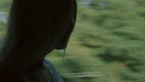 Mooi meisje die zich door het venster van de trein bevinden stock footage