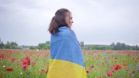Mooi meisje die zich op die een papavergebied bevinden met vlag van de Oekraïne wordt behandeld Verbinding met aard, patriottisme stock videobeelden