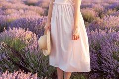 Mooi meisje die zich op het lavendelgebied bevinden met fedorahoed in haar hand stock foto