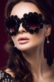 Mooi meisje in donkere zonnebril, met krullen en avondmake-up Het Gezicht van de schoonheid Royalty-vrije Stock Afbeelding