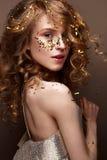 Mooi meisje in een avondjurk en gouden krullen Het model in Nieuwjaar` s beeld met schittert en klatergoud royalty-vrije stock foto's