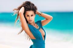 Mooi meisje in een blauwe kleding op een tropische kust Stock Fotografie