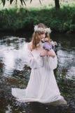 Mooi meisje in een donker bos dichtbij de rivier Stock Afbeeldingen