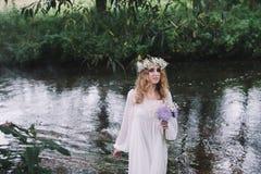 Mooi meisje in een donker bos dichtbij de rivier Royalty-vrije Stock Foto's