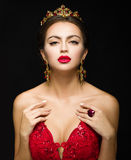Mooi meisje in een gouden kroon en oorringen op een donkere backgrou Royalty-vrije Stock Foto's
