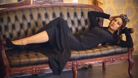 Mooi meisje in een het sexy lange kleding, een samenstelling en kroon stellen voor een fotograaf in een klassiek binnenland stock video