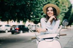 Mooi meisje in een hoed in het witte t-shirt en hoeden stellen op een autoped stock afbeelding