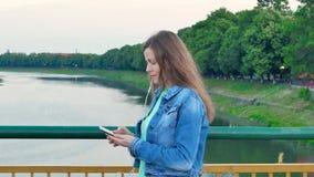 Mooi meisje in een katoenen jasje die over de brug over de rivier lopen en smartphone met oortelefoons gebruiken stock video