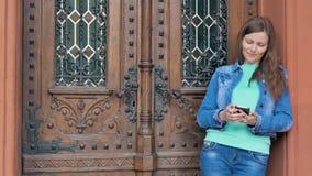 Mooi meisje in een katoenen jasje die smartphone met oortelefoons gebruiken De uitstekende bouw op de achtergrond stock videobeelden