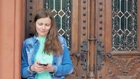 Mooi meisje in een katoenen jasje die smartphone met oortelefoons gebruiken De uitstekende bouw op de achtergrond stock video