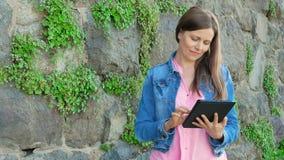 Mooi meisje in een katoenen jasje die tabletcomputer met behulp van Uitstekende muur van wilde steen op de achtergrond stock video