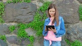 Mooi meisje in een katoenen jasje die tabletcomputer met behulp van Uitstekende muur van wilde steen op de achtergrond stock videobeelden