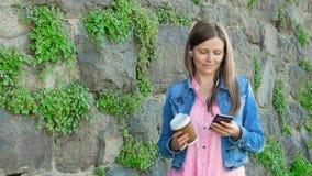 Mooi meisje in een katoenen jasje gebruikend smartphone met oortelefoons en drinkend koffie Uitstekende muur van wilde steen in stock video