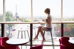 Mooi meisje in een koffie in Parijs stock afbeelding