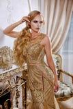 Mooi meisje in een lange gouden kleding royalty-vrije stock afbeeldingen