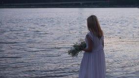 Mooi meisje in een lange witte kleding op de rivierbank stock video