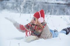 Mooi meisje in een rode hoed en sweater in de sneeuw in roze met hoofdtelefoons en sjaal stock fotografie