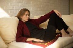 Mooi meisje in een rode laag die een rust op de laag hebben Royalty-vrije Stock Foto