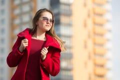 Mooi meisje in een rode laag en glazen op de achtergrond van het huis stock afbeeldingen