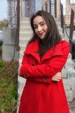 Mooi meisje in een rode laag op de achtergrond van de treden stock afbeeldingen