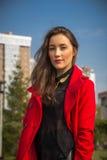 Mooi meisje in een rode laag op een achtergrond van huizen royalty-vrije stock fotografie