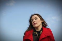 Mooi meisje in een rode laag op een blauwe hemelachtergrond stock fotografie