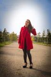 Mooi meisje in een rode laag op een parksteeg royalty-vrije stock afbeelding