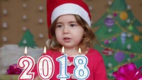 Mooi meisje in een Santa Claus-hoed die uit kaarsen blazen - close-upschot stock video