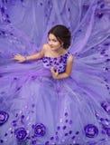 Mooi meisje in een schitterende purpere lange kleding stock fotografie