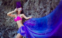 Mooi meisje in een Venetiaans masker die een lange purpere doek dragen Royalty-vrije Stock Foto