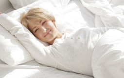 Mooi meisje in een wit bed in de ochtend, het glimlachen Stock Fotografie