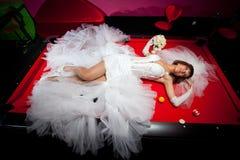 mooi meisje in een witte huwelijkskleding die op een rode lijst liggen om Amerikaanse pool te spelen royalty-vrije stock foto's