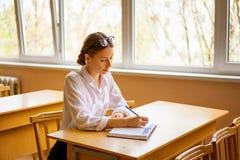 Mooi meisje in een witte overhemdszitting bij de lijst door het venster in het klaslokaal die een boek lezen stock afbeeldingen