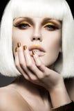 Mooi meisje in een witte pruik, met gouden make-up en spijkers Feestbeeld Het Gezicht van de schoonheid Stock Afbeeldingen
