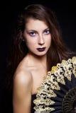 Mooi meisje in een zwarte kleding met de zwarte lange feestelijke make-up van het haar heldere nieuwe jaar in de Studio op een zw Stock Afbeeldingen
