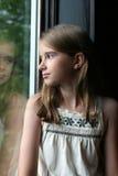Mooi meisje en haar gedachtengang bij het venster Stock Afbeelding