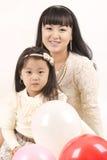 Mooi meisje en haar jonge moeder op een lichte achtergrond. Stock Fotografie