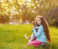 Mooi meisje en haar leuke hond die in de lente in openlucht omhelzen stock foto's