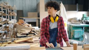 Mooi meisje gebruikend tablet in houten workshop en kijkend rond bezig met apparaat stock video