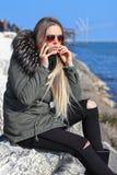 Mooi meisje Gelukkige vrouw die en op telefoon op het strand met het overzees op de achtergrond lopen spreken stock foto