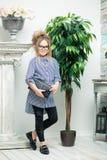 Mooi meisje in glazentribunes naast een bloem in een pot stock fotografie