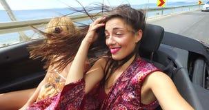 Mooi meisje het aanpassen haar terwijl het berijden van in winderig de achterbank van convertibel stock footage
