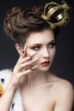 Mooi meisje in het beeld van de Koningin in de mantel met een kroon op de hoofd en lange spijkers Het Gezicht van de schoonheid royalty-vrije stock foto