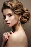 Mooi meisje in het beeld van een bruid met heldere oorringen Model met een zachte make-up in beige tonen royalty-vrije stock fotografie