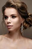 Mooi meisje in het beeld van een bruid met heldere oorringen Model met een zachte make-up in beige tonen stock afbeeldingen