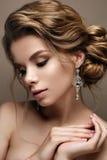 Mooi meisje in het beeld van een bruid met heldere oorringen Model met een zachte make-up in beige tonen royalty-vrije stock foto's