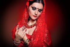Mooi meisje in het beeld van Indische vrouw in rode Sari met mooie flard acrylspijkers in oosterse stijl in de studio Stock Afbeeldingen