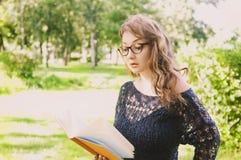 Mooi meisje in het boek van de parklezing Stock Afbeelding
