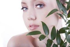 Mooi meisje Het Europese, jonge, blauw-eyed vrouw stellen met vers, groen blad Royalty-vrije Stock Foto