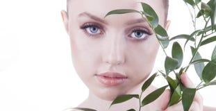 Mooi meisje Het Europese, jonge, blauw-eyed vrouw stellen met vers, groen blad Stock Fotografie
